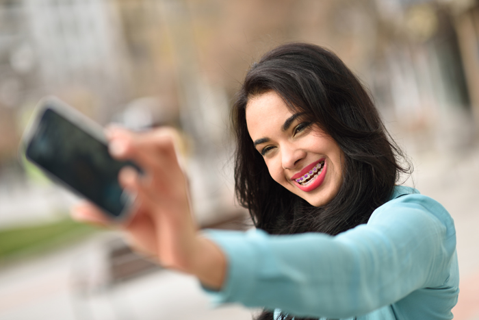 Portrait of a beautiful young woman, using braces, selfie in the street with a smartphone